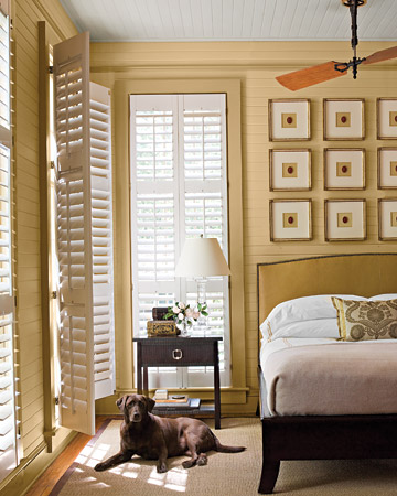 In this master bedroom, a ceiling fan with mahogany blades and tongue-and-groove wood paneling convey a cottage feel.