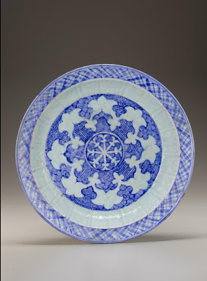Charger | Origin:  Iran | Period: mid-15th century  Timurid period | Details:  Timurid production of blue-and-white ceramics flourished in fifteenth-century Iran. The decoration of this large molded plate centers on a wheel-like motif. Its stylized octafoil design of alternating scale and wave patterns was adapted from Chinese models. The plate illustrates the Timurid interest in Chinese decorative motifs, which were adapted to Persian taste and translated into different media. | Type: Stone-paste with cobalt decoration under a translucent blue glaze | Size: H: 7.6  W: 40.0   D: 40.0  cm | Museum Code: F1999.7 | Photograph and description taken from Freer and the Sackler (Smithsonian) Museums.
