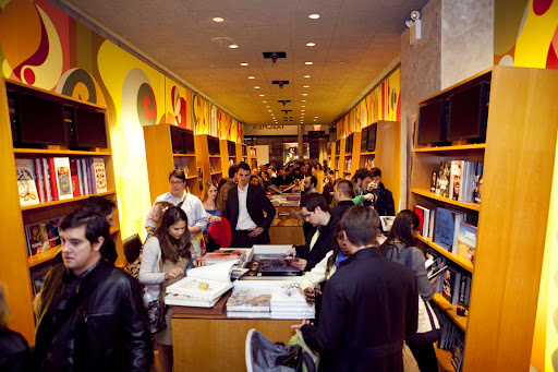 The crowd browses TASCHEN's book collection and drinks wine while they wait to meet the artist. Photo credit: Jeremiah Wilson