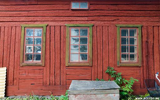 Rött timrat uthus med gröna fönsterbågar