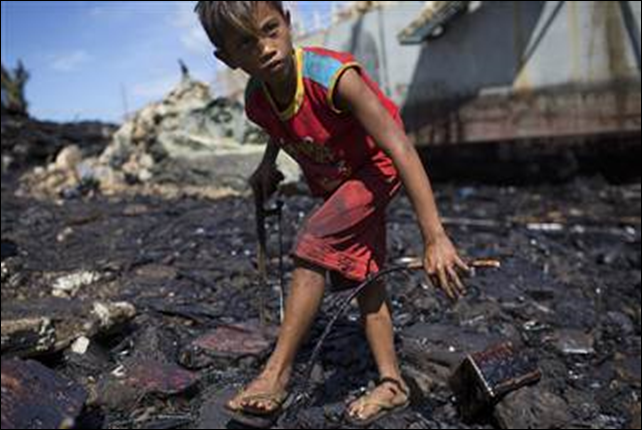 Despite thick oil slicking his hands, 14-year-old Giray Boreros uses a hacksaw Friday to collect scrap iron in the devastated fishing town of Estancia, Philippines. Typhoon Haiyan hit here with such force that a barge ran aground, spilling approximately 1.4 million liters of oil into the bay, according to the town's mayor. Photo: Jim Seida / NBC News