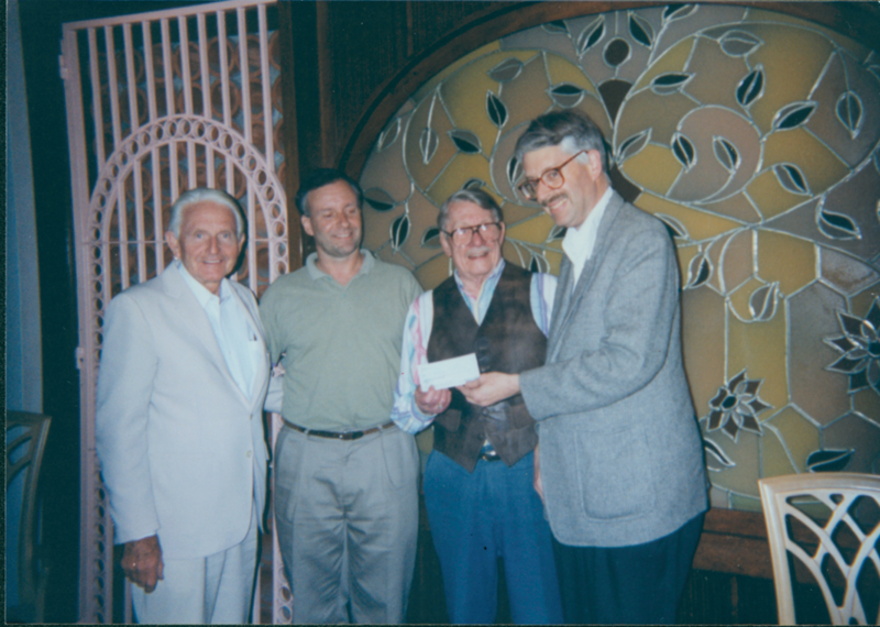 Hal Call contributes $55,000 to the Hal Call Scholarship Fund at the Los Angeles Crowne Plaza Hotel. Accompanying Hal Call are Reid Rasmussen (far left), Walter Williams (second from left), and David Cameron (far right). 1996.