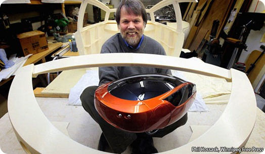 "PHIL.HOSSACK@FREEPRESS.MB.CA<br />101220-Winnipeg Free Press<br />Holding a 1/4 scale replica, Jim Kor sits in plastic body panels for his electric car ""Urban"". Panels are ""printed"" with a 3D printer out of plastic for the vehicle....Murray's tale."