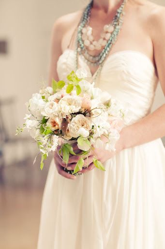 The bride held a loose bouquet of blooms, vines, and foliage.