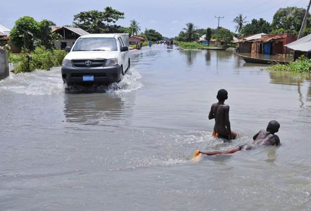 Chidren wade through a flooded road in Idah Local Government Area in Nigeria's central state of Kogi, 27 September 2012. Nigeria's worst flooding in decades has displaced more than 600,000 people in the centre of the country over the past week and stranded some villagers on rooftops. Afolabi Sotunde / REUTERS