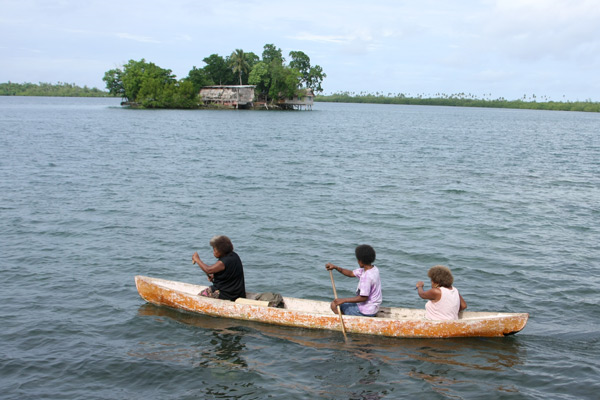 Residents paddle a canoe past past artificial coral islands in Langa Langa Lagoon, Malaita island, Solomon Islands. The Prime Minister says it is time for residents to move into resettlement before sea level rise becomes a huge threat. Photo: Globe Spots