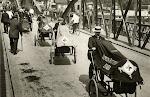 Eerste Wereldoorlog. Over een brug rijdt een hele stoet Rode Kruis medewerkers op fietsen met fietskarren ervoor, waarmee gewonden vervoerd kunnen worden. Op een ervan staat: 'Vereen. Rotterdamse EHBO'. Rotterdam, Nederland, 1914.