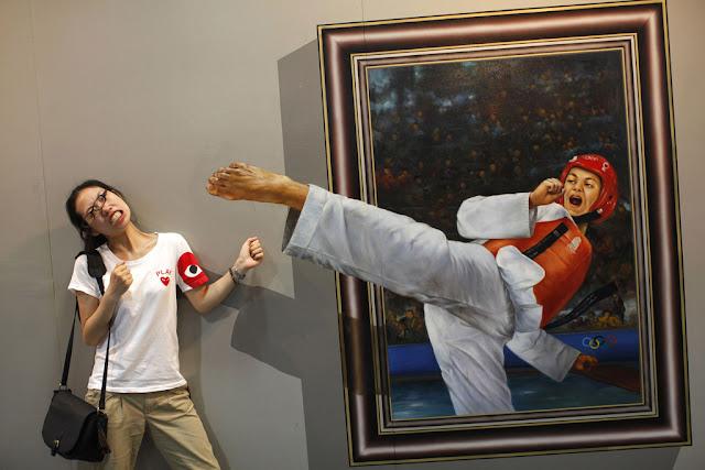 ハイキックが顔面を直撃したかのようなポーズでおどける女性。中国・杭州での3D絵画の展覧会で。(ロイター=共同)