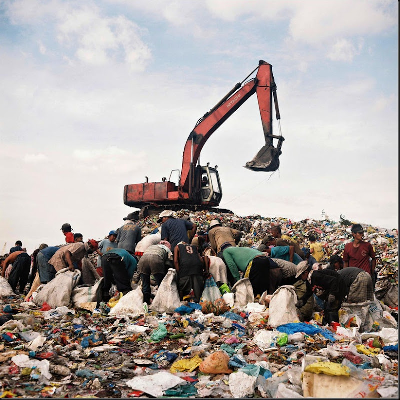 Hundreds of families of scavengers eke out a living at a large garbage dump in Manila, Philippines called Happyland. The ironic name comes from the word hapilan, a local term for a dump site. Happyland scavengers forage the large mound of garbage for any recyclable materials such as plastics, bottles, and metal parts where they exchange them at nearby junk shops. Scavengers earn a measly eighty pesos (USD 2.00) for a day's work.