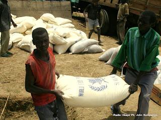 Deux  hommes  transportent  un  sac  de vivre en provenance d'un convoi du  Programme Alimentaire Mondial(PAM)  ce 1/01/2003 dans le Camp des déplacés à Geti en RDC, lors de la visite de Jan Egland, Secrétaire générale des Nations Unies en charge des affaires Humanitaire. Radio Okapi/ Ph. John Bompengo