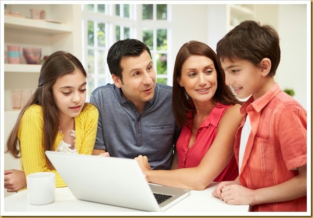Family Looking at Laptop Over Breakfast