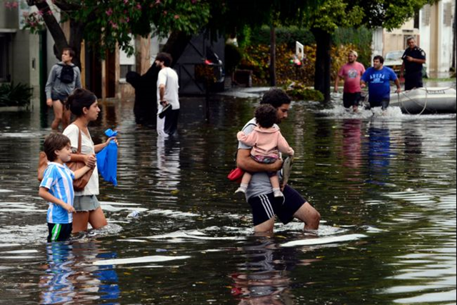 People wade through flooded streets as the water starts subsiding in La Plata, located 63 km south of Buenos Aires, on 3 April 2013 after a powerful storm pummeled the Argentine capital overnight from Tuesday to Wednesday. Photo: Daniel Garcia / AFP / Getty Images