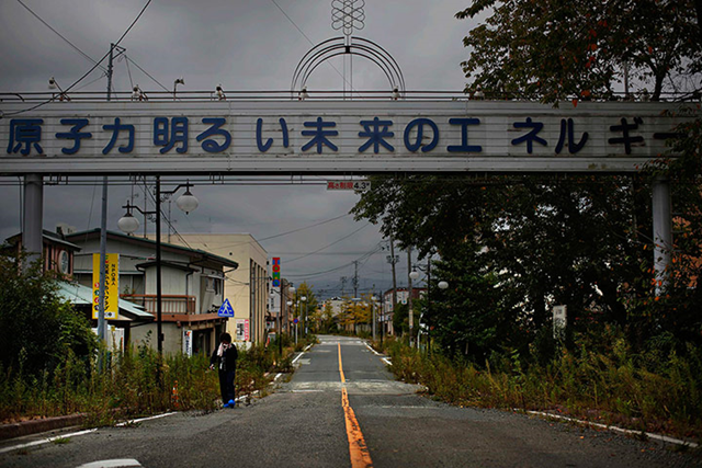 A woman paying a brief visit to her home walks under a sign reading 'Nuclear power – the energy for a better future', at the entrance of the empty Futaba town. Decades ago the citizens ofFutaba took such pride in hosting part of the Fukushima Daiichi nuclear complex that they built a sign over a promenade proclaiming that atomic power made their town prosperous. Photo: Damir Sagolj / Reuters