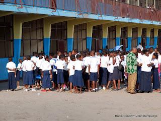 En avant plan de droite à gauche en chemise verte un enseignant en conversation avec des élèves habillés en bleu blanc devant le bâtiment d'une école à Kinshasa. Radio Okapi/ Ph John Bompengo