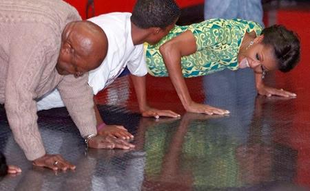 Michelle Obama fa le flessioni con l'arcivescovo Desmond Tutu a un evento per promuovere la prevenzione contro l'HIV tra i giovani, in uno stadio a Città del Capo, in Sudafrica, 23 giugno 2011