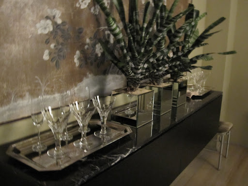 Extra glasses are placed behind the dining room table -- in a location that is easy to get to if someone needs something during dinner.