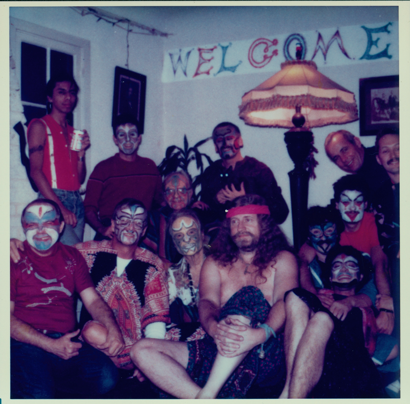 A Radical Faeries welcome home party with members in face paint, including Harry Hay (seated, center) and John Burnside (in front of Harry). Circa early 1980s.