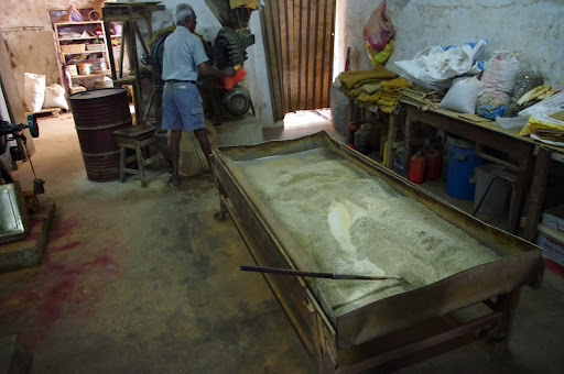 A worker grinds and sifts spices into powder.