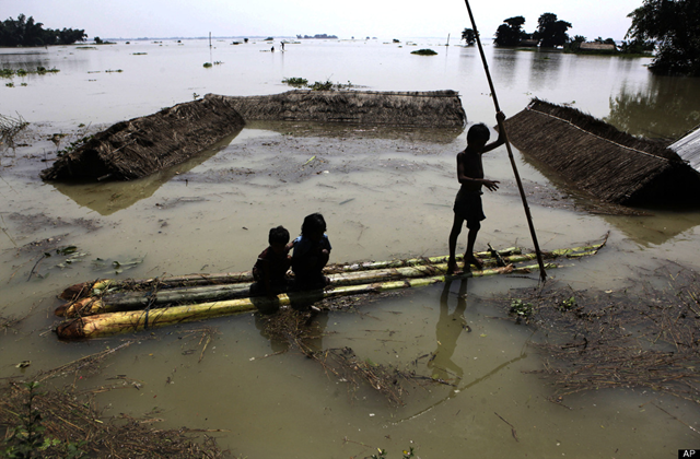 Indian children use a raft, made of banana plants, to wade through flood waters at Burhaburhi village, about 65 kilometers (40 miles) east of Guahati, India, 29 June 2012. Anupam Nath / AP Photo