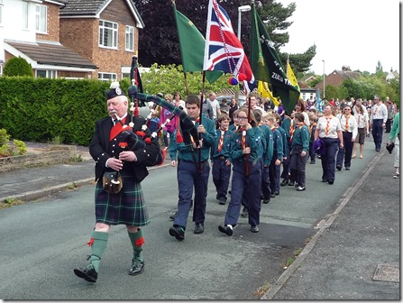 Scottish Piper Reg Flower leads the procession through Wistaston
