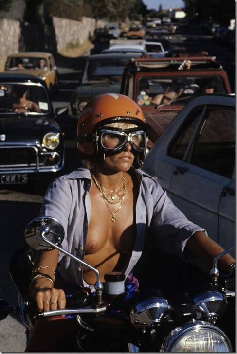 En France, à Saint-Tropez, en juillet 1979, durant les vacances d'été, la mode des plages de nudistes, une femme motard, sur sa moto, la chemise ouverte laissant apparaître ses seins nus.