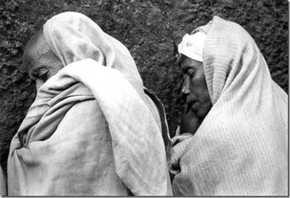 Pilgrims wrapped in theirs netelas (ceremony cloth) praying outside during a religious worship in Bet Madhane Alem church. . Ethiopian Orthodox Coptic have a deep faith  with their roots sank in the early Christians and with Judaism influences