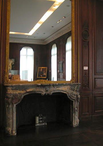 A gorgeous, gilded mirror hangs over the marble fireplace of the gallery.
