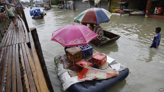 Residents use makeshift floats as others cross a makeshift bridge built over a flooded road in suburban Pasig, east of Manila, Philippines, 15 August 2012. AP