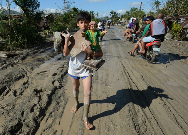A resident carries a religious statue along a muddy road in the town of New Bataan, compostela province, 6 December 2012. Ted Aljibe / AFP / Getty Images