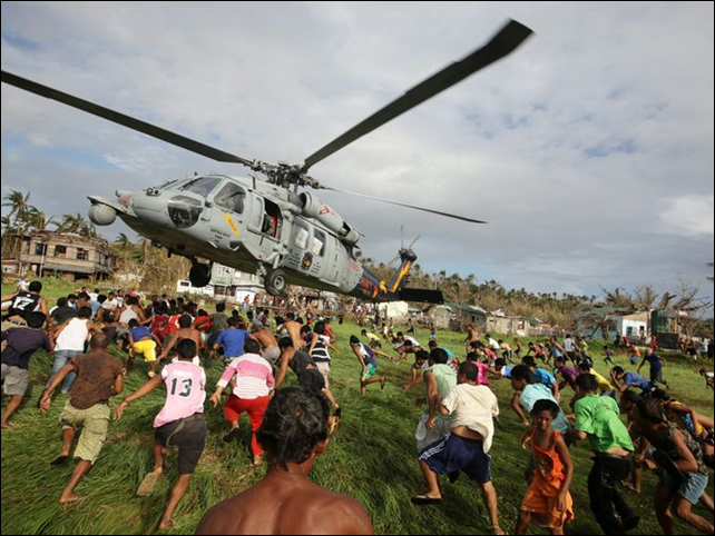 Filipinos rush to get relief goods from a U.S. Navy helicopter in the devastated town of Salcedo, Samar island province, Philippines on 16 November 2013. Photo: Francis R. Malasig / EPA