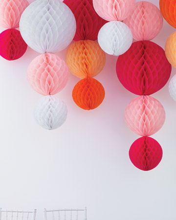 Paper chandeliers of tissue orbs stapled to narrow ribbon and hung from the ceiling will elicit oohs and aahs from your guests. (marthastewartweddings.com)