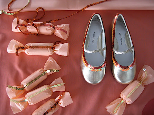 A cute shot of the favors and slippers, all decked out in sequins.