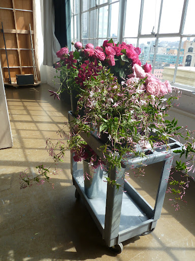 A cart holds roses, clematis, and jasmine. We moved it to the sun so the flowers would open up.