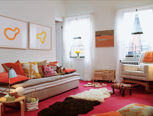 I love a long, low sofa in the living room.  The bold colors and patterns of the pillows look great with the neutral tones.  The side table is actually a stool that was cut to work with the height of the sofa.  So smart!