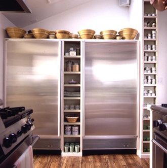 Martha wastes no space in her kitchen. Even the space between refrigerators is used for more shelving.