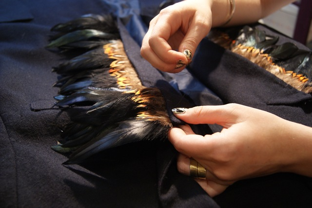 Using your threaded hand needle, you will need to work your way down the lapel using a running stitch (sewing up and down) to secure your feathers into place. Then remove your pins. Useful tip: make sure your stitches are fairly small so you won't be able to see the stitches from the front and also the feathers are nice and secure.