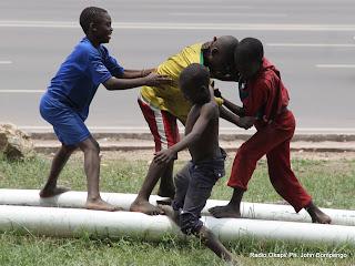 Des enfants sans demeure fixe (shégués)  jouent en face du siège de la Ceni le 12/10/2011 à Kinshasa. Radio Okapi/ Ph. John Bompengo