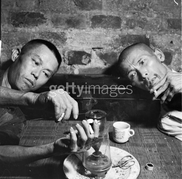 Opium Smokers circa 1955, Narcotic addicts in the British Crown Colony of Hong Kong heat a dab of opium over the flame of an oil lamp until it is dry enough to smoke from a pipe. (Photo by Evans:Three Lions:Getty Images).jpg