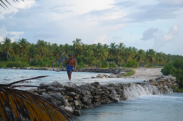A local villager in Beru, Kiribati crosses a causeway carrying his bike at high tide with the water lapping at his feet, 6 November 2006. Only a few years earlier, this sight was highly uncommon but is now experienced on a regular basis. Photo: Jeremy Mather / flickr