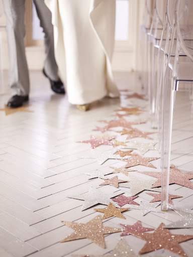 Sprinkle glitter over paper stars and tape them down the aisle for a radiant runner. (Martha Stewart Weddings)
