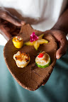 The chef holds a combination platter of star anise, local fish, scallops, and a vegetable blend.