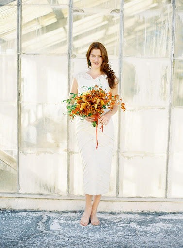 A punchy orange bouquet pops against a white dress. The loose arrangement highlights the dress's streamlined silhouette.