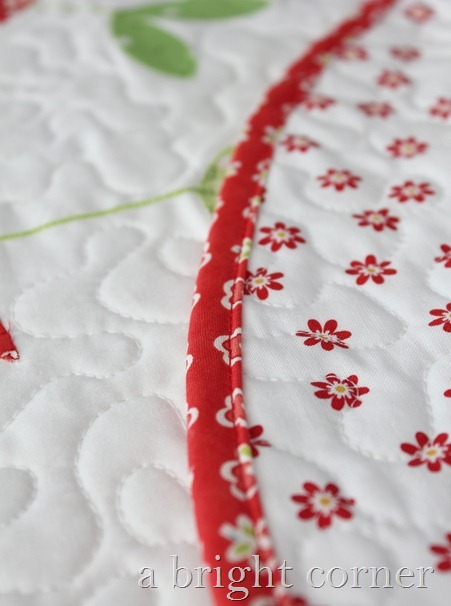 Sprouts table topper with red binding