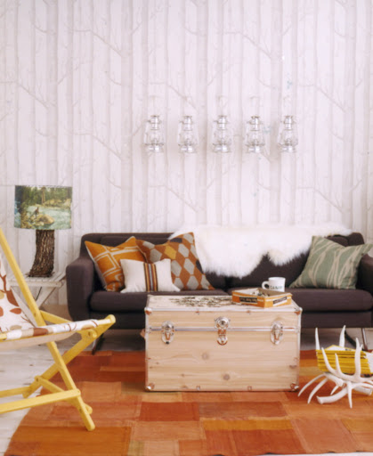 So many different camp-inspired products come together in this room: a trunk, a rustic lamp, a lawn chair, and lantern sconces. (blueprintmagazine.com)