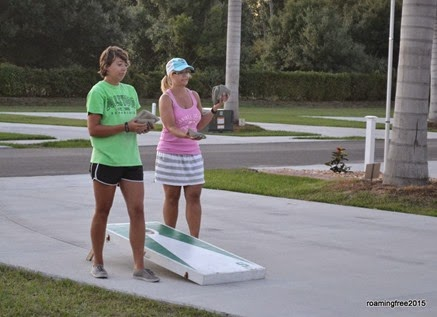 Teaching Emily and her parents how to play cornhole