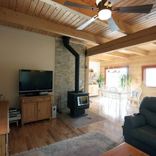 Living room with wood stove and dining area in background  (Foto by Ted Grant)