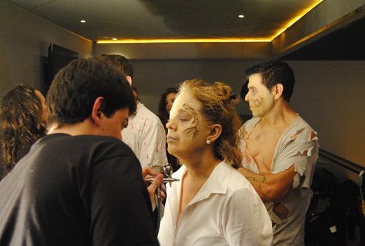 Santiago Gijón (de espaldas) retoca las falsas heridas de una zombi.