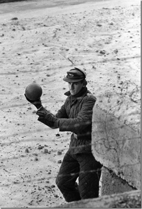 An East German guard throws a ball back to a child on the West German side of the Berlin Wall in June 1962, photographed by Paul Schutzer for LIFE.