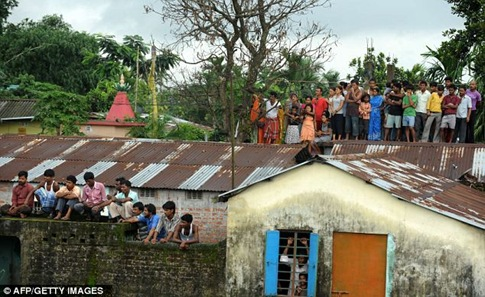 Villagers grab a rooftop view to watch the excitement unfold in Prakash Nagar village
