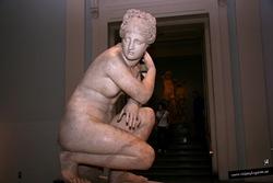 Afrodita en el baño. Estatua de mármol de un desnudo en cuclillas